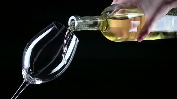 White Wine Being Poured Into a Wineglass, Black, Closeup, Slowmotion