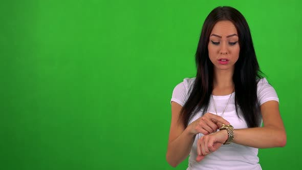 Cover Image for Young Pretty Woman Points on Watch (Show Time) - Green Screen - Studio