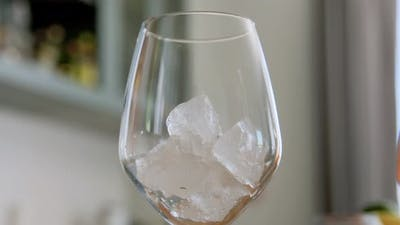 Hand Dropping Ice to Wine Glass at Home
