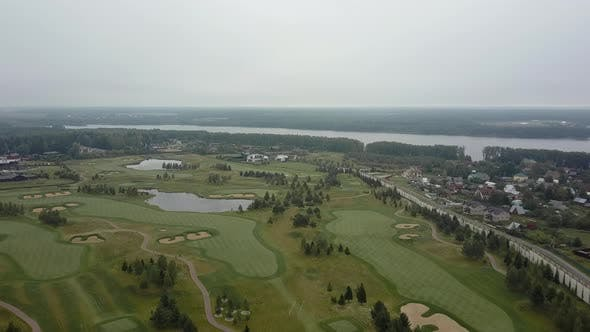 Thumbnail for Aerial Shot of Golf Fields and Township Near the River