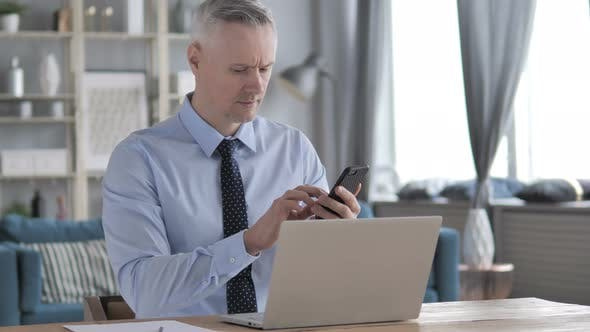 Thumbnail for Gray Hair Businessman Using Smartphone at Workplace