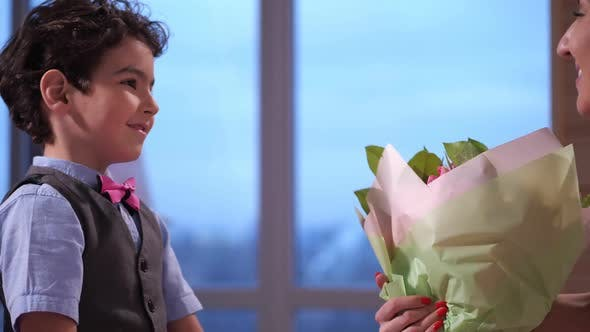 Thumbnail for Close Up Adorable Son Presenting Flowers To Mom