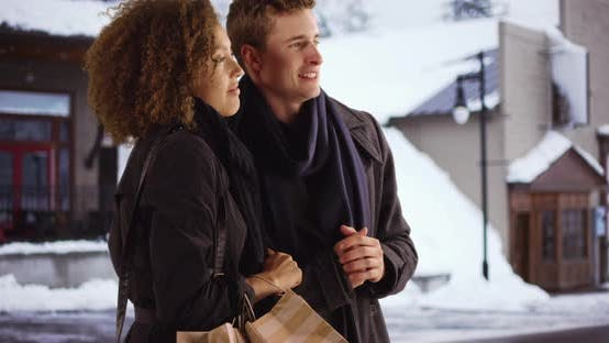 Thumbnail for Happy multiethnic couple shopping outside on winter day