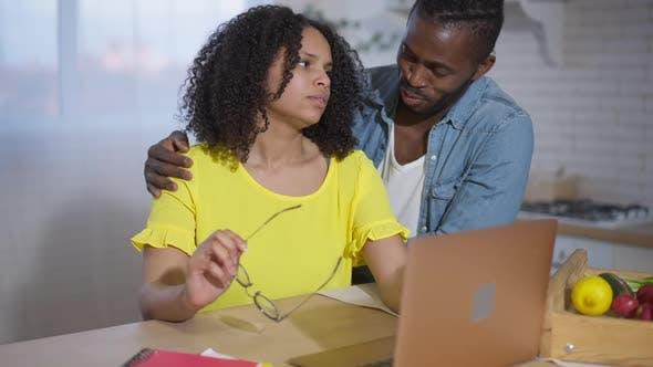Intelligente Afroamerikanerin absorbiert, die online arbeitet als liebevoller Mann, der Ehepartner umarmt