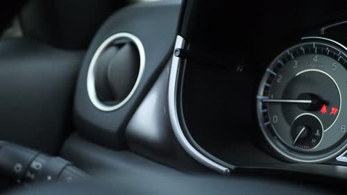 Close Up of Car Dashboard with an Engine Speed Dial and Tachometer