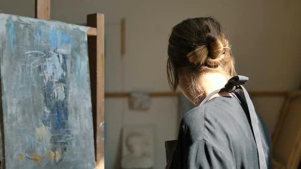 Thumbnail for Frau Künstlerin macht blaue Striche der Farbe auf Leinwand im Studio
