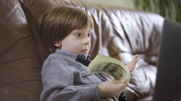 Cover Image for The Little Boy in Jeans Jacket Sitting on the Leather Sofa in Front of Laptop Playing with the Money