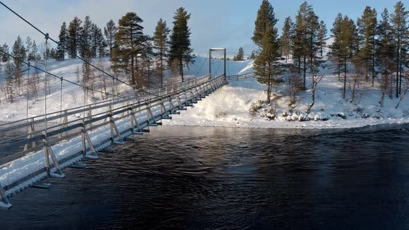 Thumbnail for Aerial Shot Of River And Suspension Bridge With A Winter Background