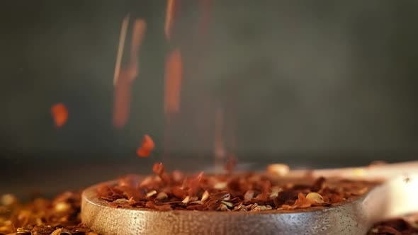Thumbnail for Flakes of Red Hot Chili Pepper in Wooden Spoon Closeup on a Kitchen Table.