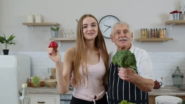 Senior Grandfather with Granddaughter Recommending Eating Raw Vegetable Food. Vegetable Diet