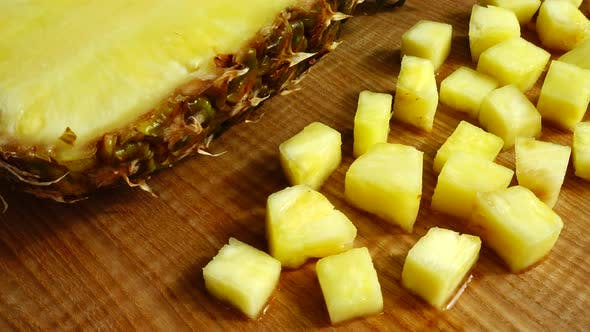 Pieces of pineapple on a cutting wooden board.