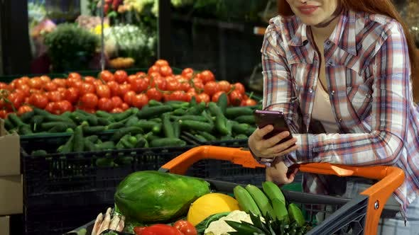 Thumbnail for Girl Uses Smartphone at the Hypermarket