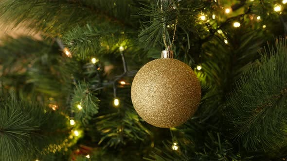 Thumbnail for Warm lights and gold bauble with sequins hanged on the branch 4K 2160p 30fps UltraHD footage - Golde