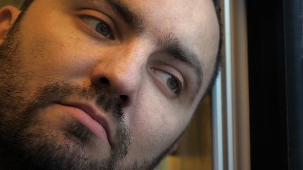 Thumbnail for A tired man's face in a train.