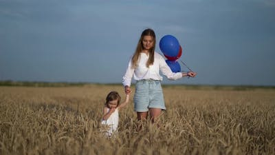 Mother with Daughter and Balloons Walking on Wheat Field