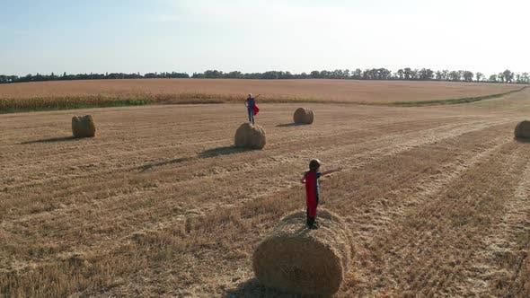 Drone Shot of Superheroes in Pose on Straw Stacks