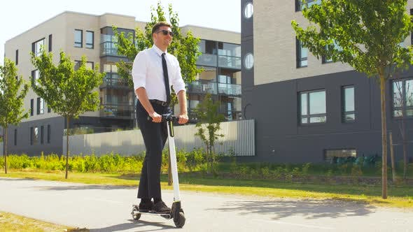 Young Businessman Riding Electric Scooter Outdoors