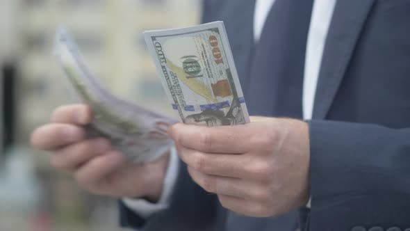 Male Caucasian Hands Counting Money on Urban City Street. Unrecognizable Wealthy Man Holding Pack of