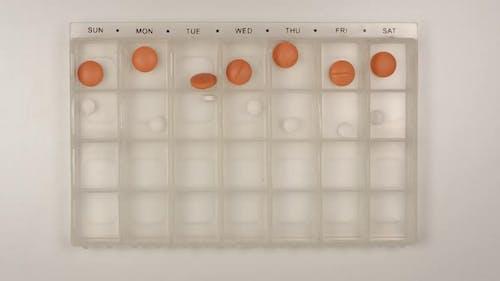 Male nurse hand puts down a pills into a pill organizer