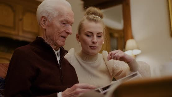 Thumbnail for Granddaughter Looking At Photo Album With Grandfather