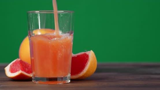 Der Saft aus den Grapefruits gießt in ein Glas