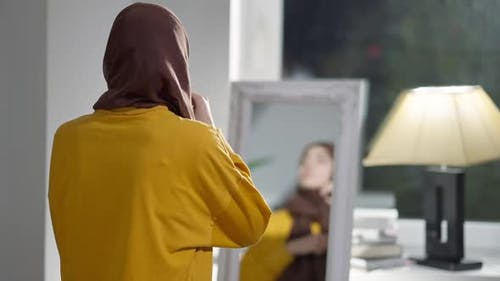 Rückansicht der schlanken jungen Frau, die Kopftuch anpasst, die sich lächelnd der Kamera zuwendet