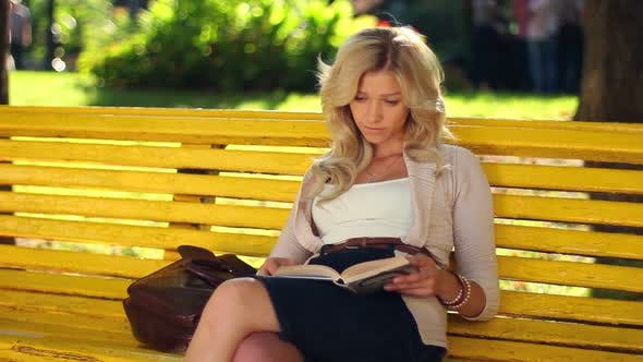 Thumbnail for Young Adult Woman Girl Reads Book in Park Yellow Bench Waiting