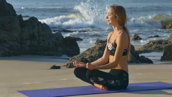 Blond Girl Relaxes in Yoga Pose By Ocean Waves