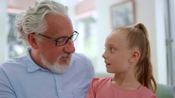 Thumbnail for Grandfather Talking with Granddaughter at Home. Girl Sitting on Grandfather Laps