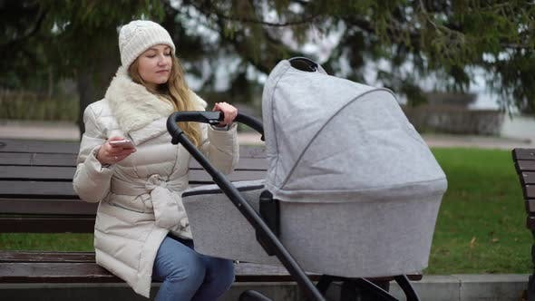 Thumbnail for Happy Mother with Smartphone Using App. She Sitting on the Bench , Baby Sleeping in Pram