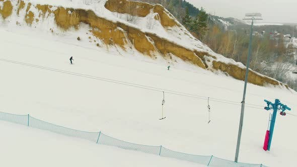 People Ski Down Wide Snowy Trail with T-bar Lift Aerial View