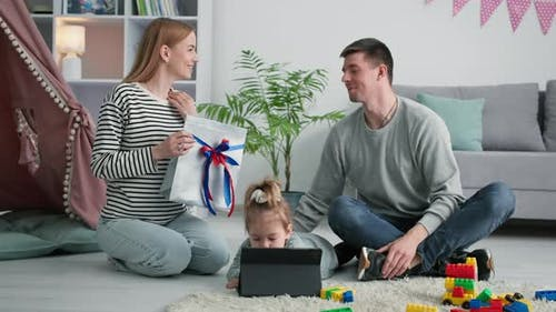 Fathers Day Loving Wife Gives Her Husband Present While Female Child Plays on Tablet During Family