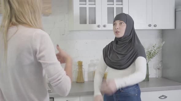 Thumbnail for Camera Approaching To Muslim Woman in Hijab Arguing with Blond Caucasian Friend at Home. Two Women