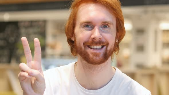 Thumbnail for Redhead Beard Man Gesturing Victory Sign in Cafe