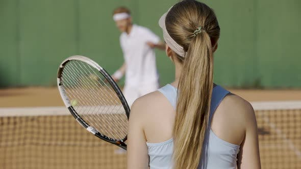 Thumbnail for Female hitting tennis ball with racket at sports club, playing with opponent