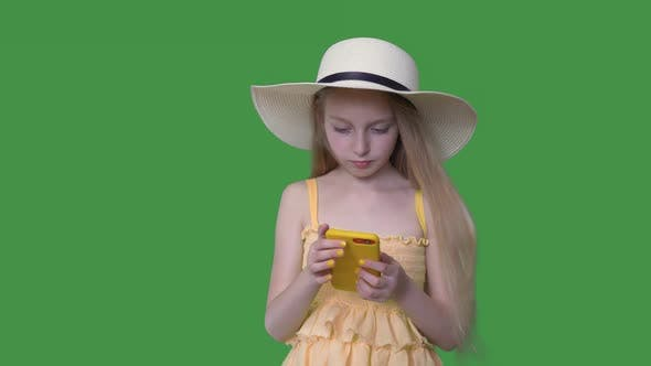 Thumbnail for Young Girl in Hat and Yellow Dress Using Mobile Phone on Transparent Green Background
