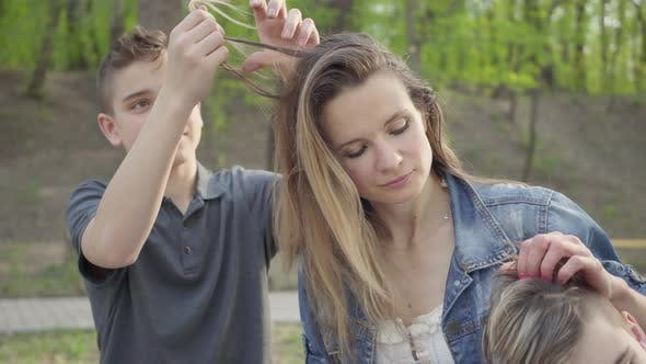 Thumbnail for Son Making a Hairdress To His Mom or Nanny While They Are in the Park on Sunny Spring Day