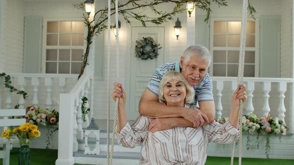 Thumbnail for Senior Couple Together in Front Yard at Home. Man Swinging Woman During Coronavirus Quarantine