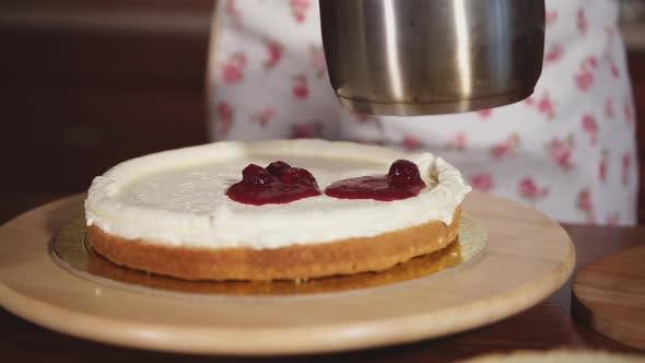 Thumbnail for Konditorei legt eine Kirschmarmelade auf Kuchen mit Schlagsahne