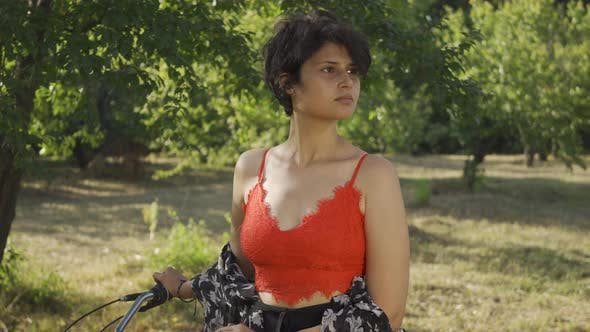 Thumbnail for Portrait of Pretty Young Woman with Short Black Hair Standing in the Garden or Park with Her Bicycle