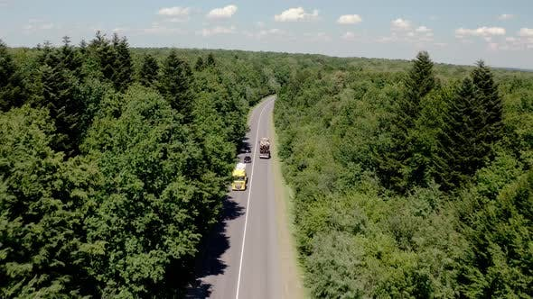 Aerial View of White Truck with Cargo Semi Trailer and Several Cars Moving on Road in the Forest