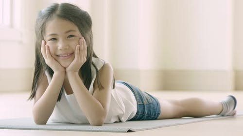 Portrait of a cute little Asian girl lying down on the floor