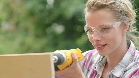 Thumbnail for Woman wearing safety goggles drilling plywood with electric drill
