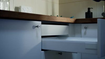 Housewife Putting Cutlery in Cupboard Drawer at Kitchen Indoors