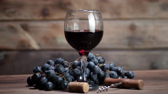 The Glass of Red Wine on the Table Slowly Rotates. On a Wooden Background