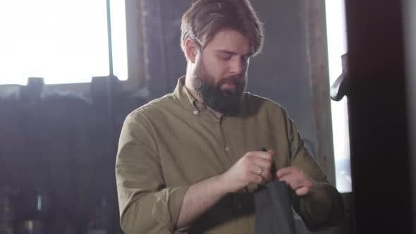 Thumbnail for Worker Putting on Apron in Workshop