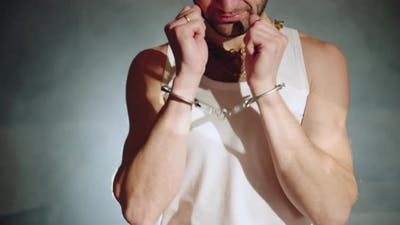 Gangster with Handcuffs on His Hands is Trying to Free Himself
