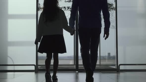 Cover Image for Silhouettes of Caucasian Man and Girl Walking Out the Airport Through Glass Door