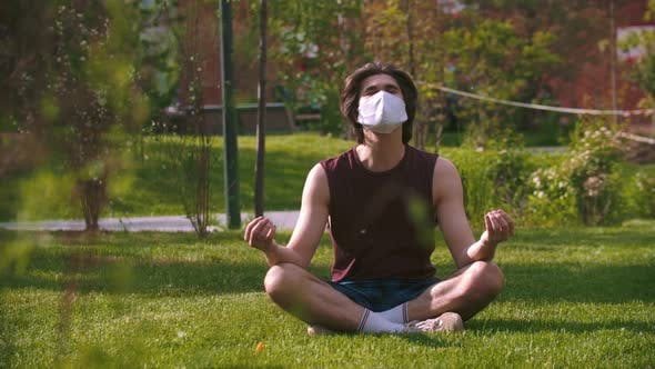 Thumbnail for A Young Man in the Medical Mask Sitting on the Grass in the Park and Meditating