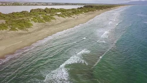 Sandy Beach Spit Washed By the Water on Both Sides. Aerial Survey. Slow Motion